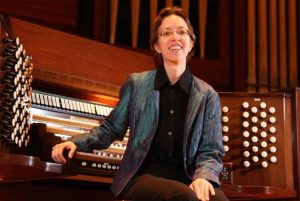 Isabelle Demers in Concert attire, sitting at an organ console with 4 manuals